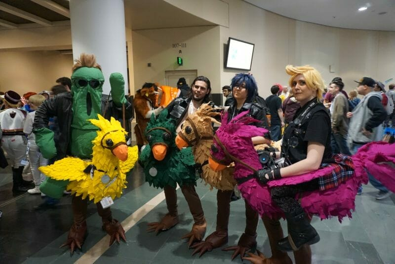 Four cosplayers dressed as characters from Final Fantasy XV. They are riding hand-made chocobos.