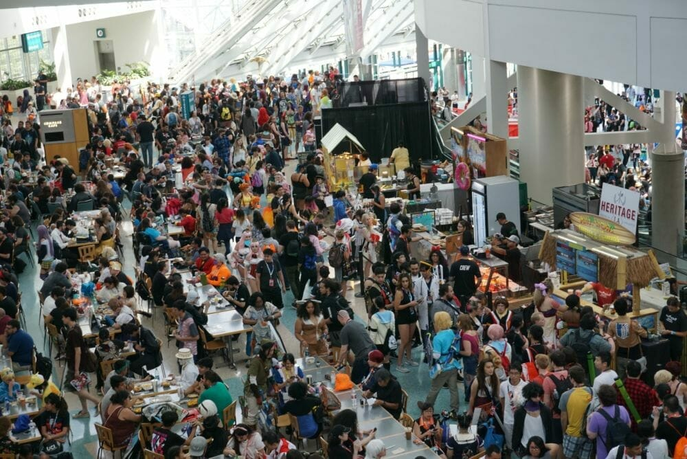 An overhead photograph of the Anime Expo main floor. The tile is completely obscured by people.