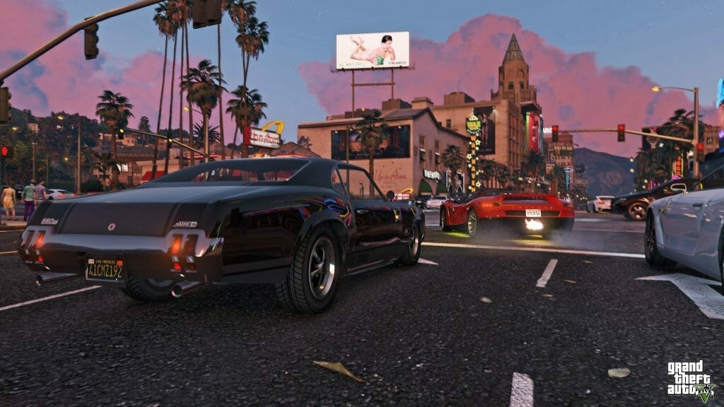 A black car drives along a city street. A white billboard featuring a naked man is directly above the vehicle.