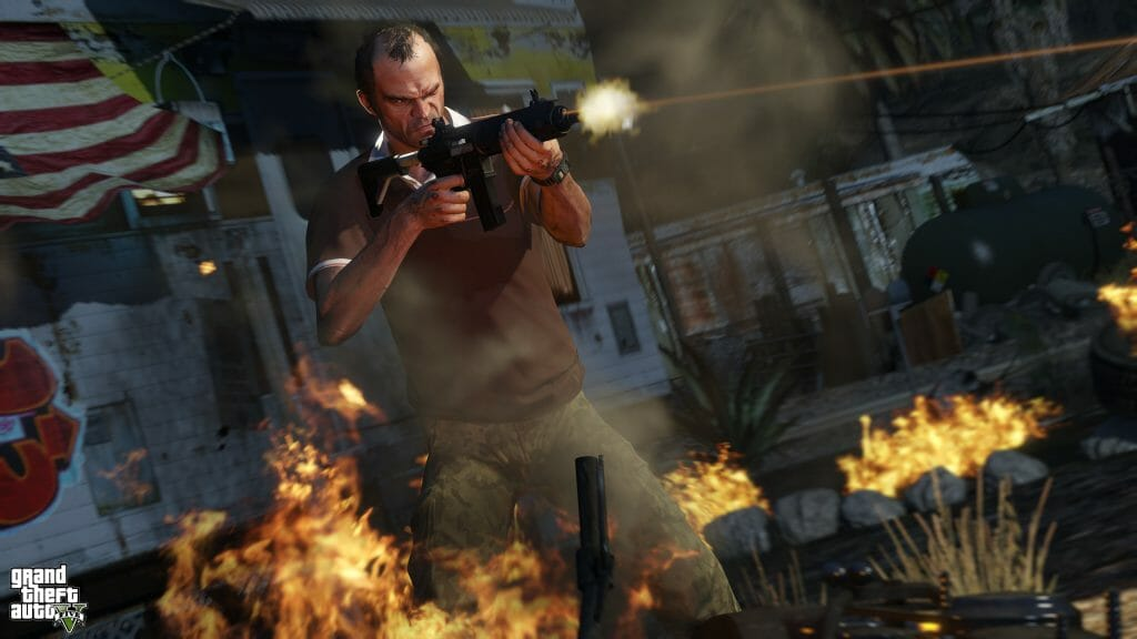 Grand Theft Auto V Still - A man holding a machine gun opens fire while standing in a pile of flaming rubble.