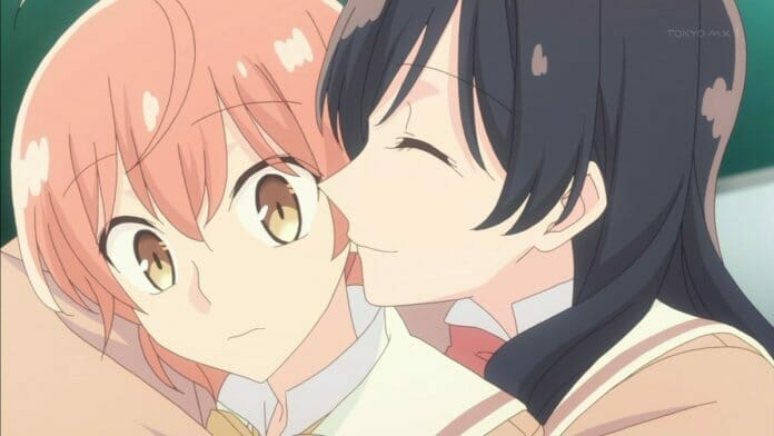 Bloom Into You anime still - a black-haired girl smiles as she wraps her arm around a pink-haired girl.