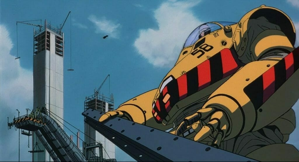 Patlabor Movie Still - A yellow robot holds a girder under a blue sky.