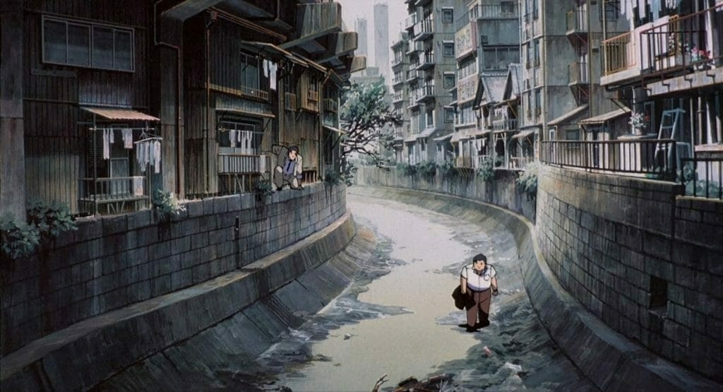 Patlabor Movie Still - A man walks sullenly through a flooded avenue, flanked by buildings on either side.