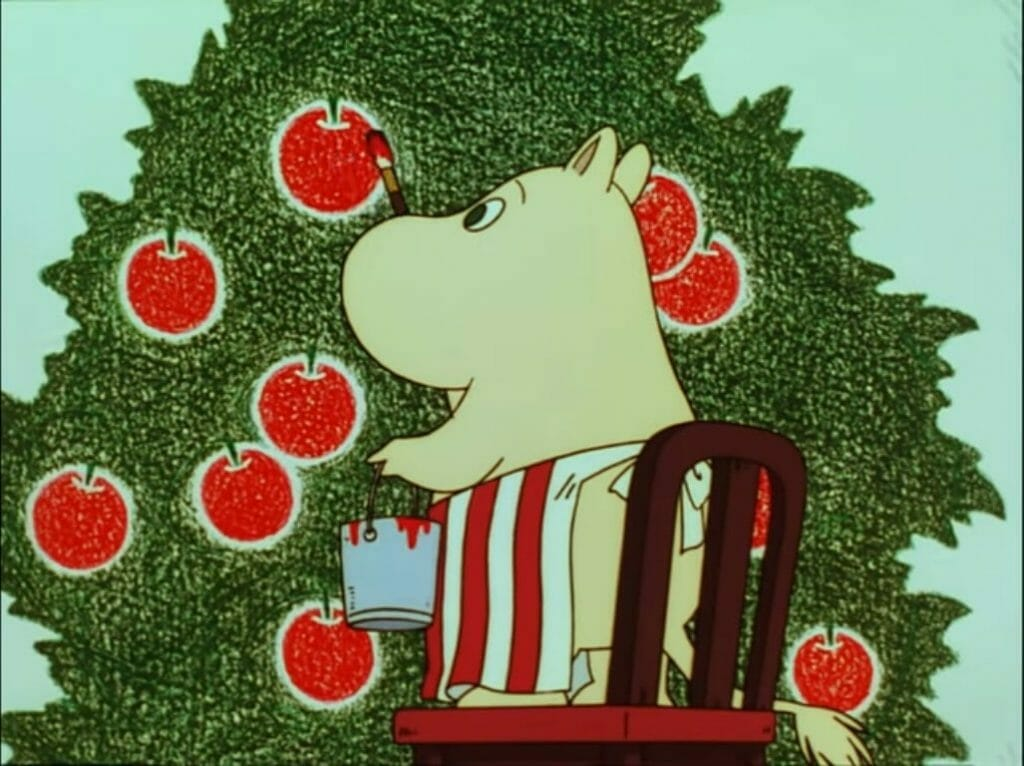 A screenshot from Tanoshii Moomin Ikka. Moominmamma paints an apple tree on the lighthouse's interior wall. She is standing on a chair, holding a paint-bucket with red paint in her left paw and a paintbrush with red paint in her right paw