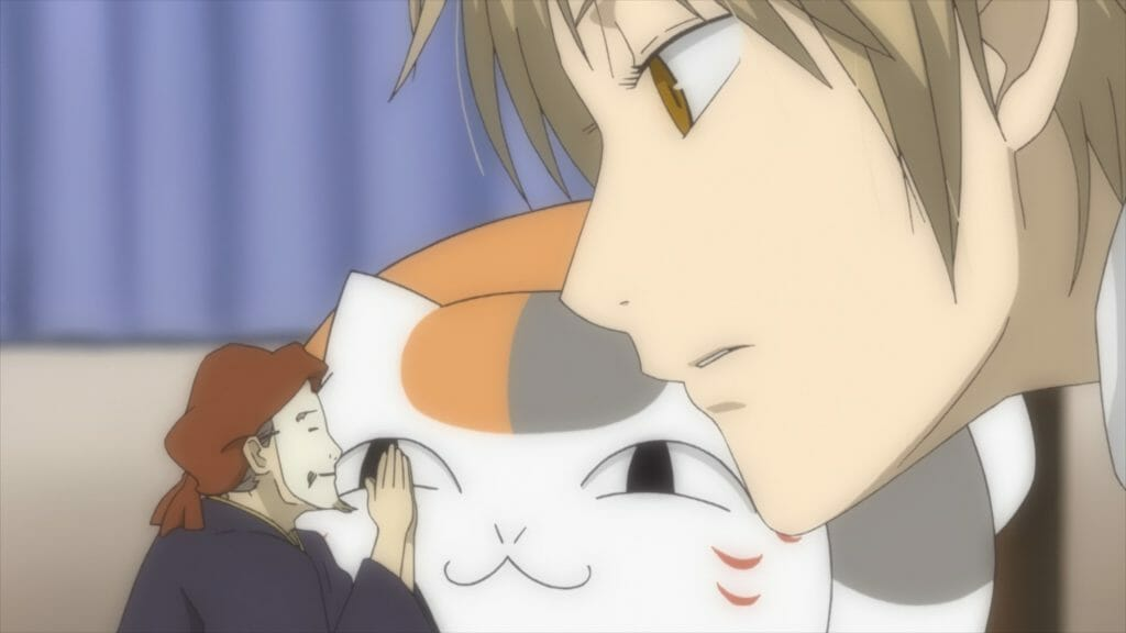 Natsume's Book of Friends Anime Still - A man with blonde hair talks to a tiny man wearing a mask. A cat watches from the background.