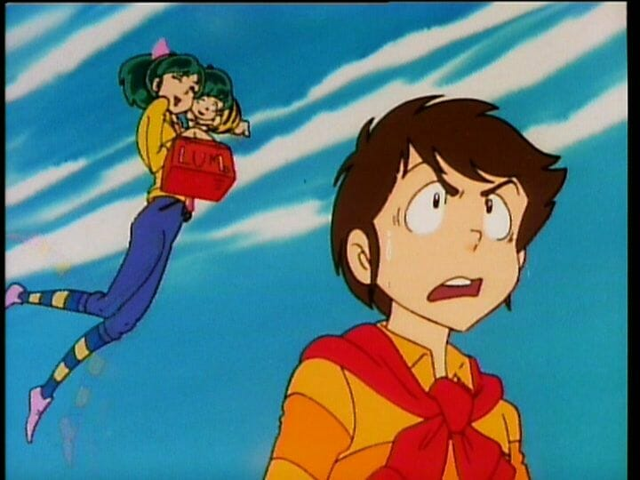 Urusei Yatsura Anime Still - A brown-haired man in a yellow top looks to the right. Behind him, a green-haired girl wearing jeans and a yellow top floats as she hugs a small green-haired child.