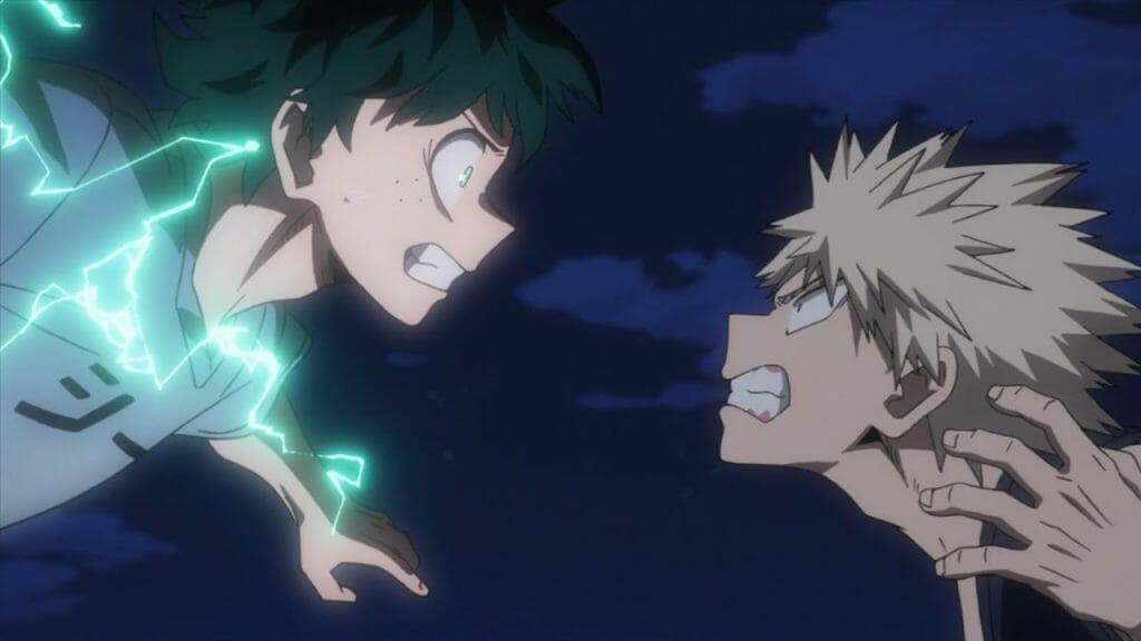 My Hero Academia anime still - a boy with shaggy green hair charges as a blonde boy. The boy with green hair crackles with energy.