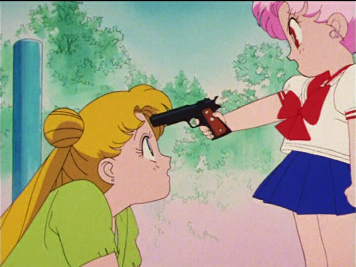 Sailor Moon anime still - A blonde girl stares at a young girl with pink hair. The girl with pink hair has a gun to the blonde girl's head.
