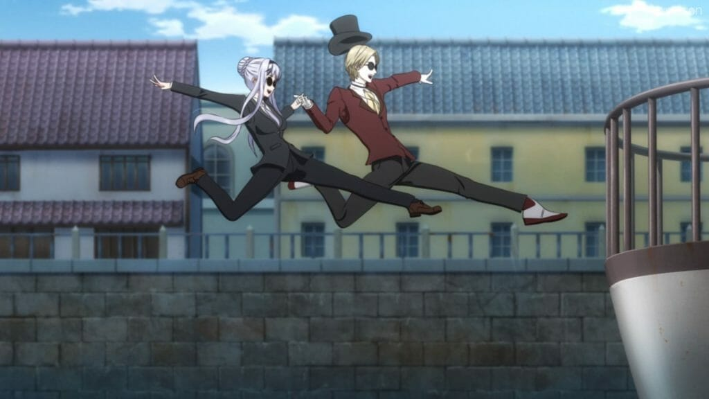 A smiling blonde man and blue-haired woman, both in suits, jump playfully toward a ledge.