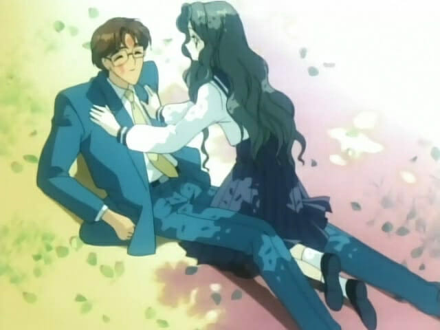 A dark-haired woman lays atop a brown-haired man in a suit.