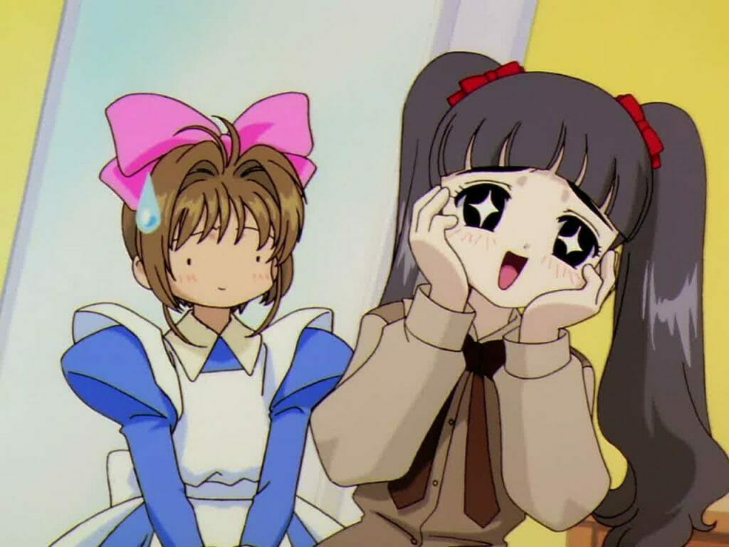 A black-haired girl with pigtails wears an elated expression as a brown-haired girl in a blue dress and pink bow stares, nonplussed.