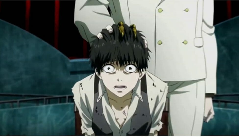 A black haired man stares at the camera in horror. A person stands behind him, gripping the top of his head.