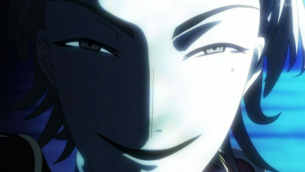 A man smirks evilly at the camera. Half his face is obscured by shadow.