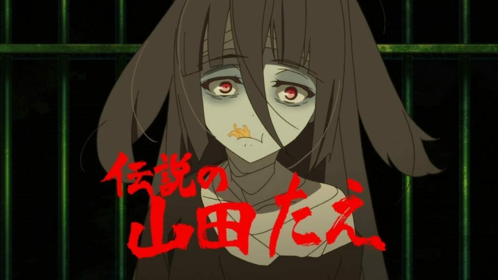 """A black-haired zombie girl stares blankly as she gnaws on dried squid. The words """"The Great Tae Yamada"""" are presented in red text below her face."""