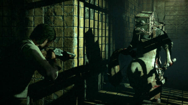 A still from The Evil Within that features a man aiming a pistol at a person who has a safe on his head.