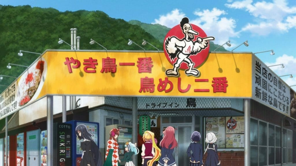 Six women stand in front of a storefront with a yellow sign, emblazoned with a red bubble that has a drawing of a smiling chicken inside it.