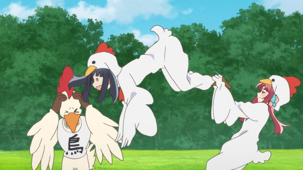 A black-haired woman in a chicken costume jumps at a gigantic chicken mascot. A red-haired woman, also in a chicken costume, holds the other woman back.