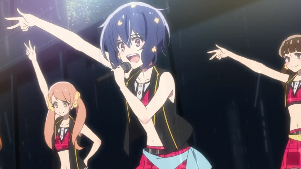 Still from Zombie Land Saga Episode 6, which depicts a black-haired idol smiling brightly as she addresses a crowd from the stage.