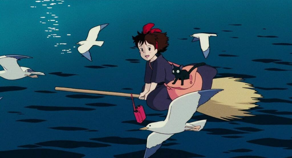 Still from Kiki's Delivery Service, which features Kiki and Jiji flying on a broom over the ocean.