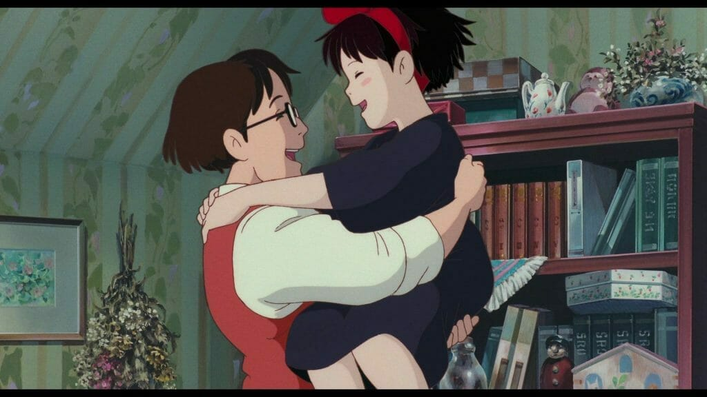 Still from Kiki's Delivery Service, which features Kiki smiling as she hugs her father, Okino.