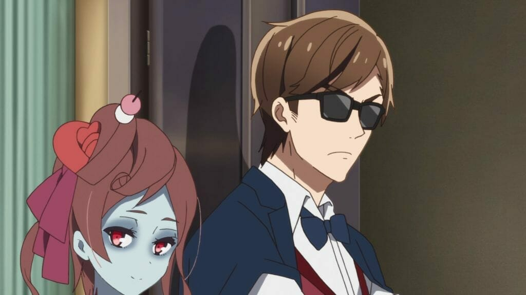 Still from Zombie Land Saga Episode 10, which features a brown-haired zombie woman standing beside a man in sunglasses. Both are wearing worried expressions