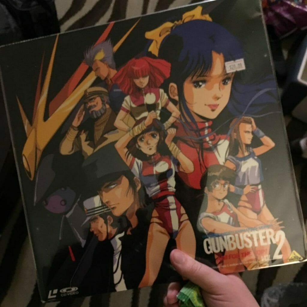 Photo of a hand holding the laserdisc for Gunbuster 2