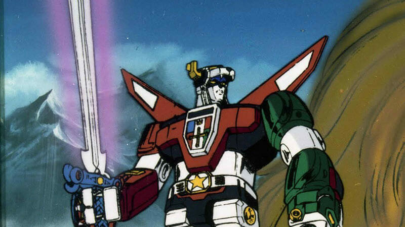 Upper body shot of Voltron: a giant multicolored robot holding a pink laser sword.