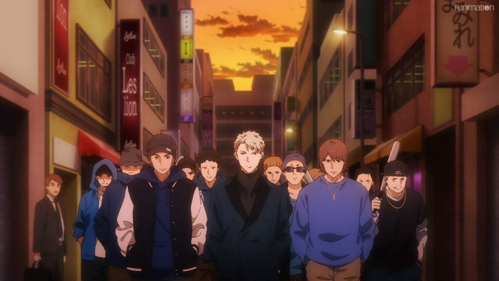 Still from Ikebukuro West Gate Park that depicts a blonde man in a suit, who stands in front of a crowd of people in blue.