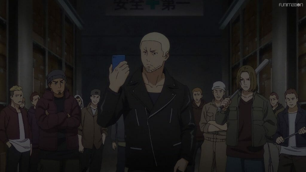 Still from Ikebukuro West Gate Park that depicts a blonde man who stares at a cell phone as he stands in front of a crowd of people.