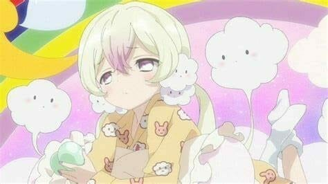 A blonde woman in yellow pajamas gazes sleepily at the camera. She's surrounded by white puffs.