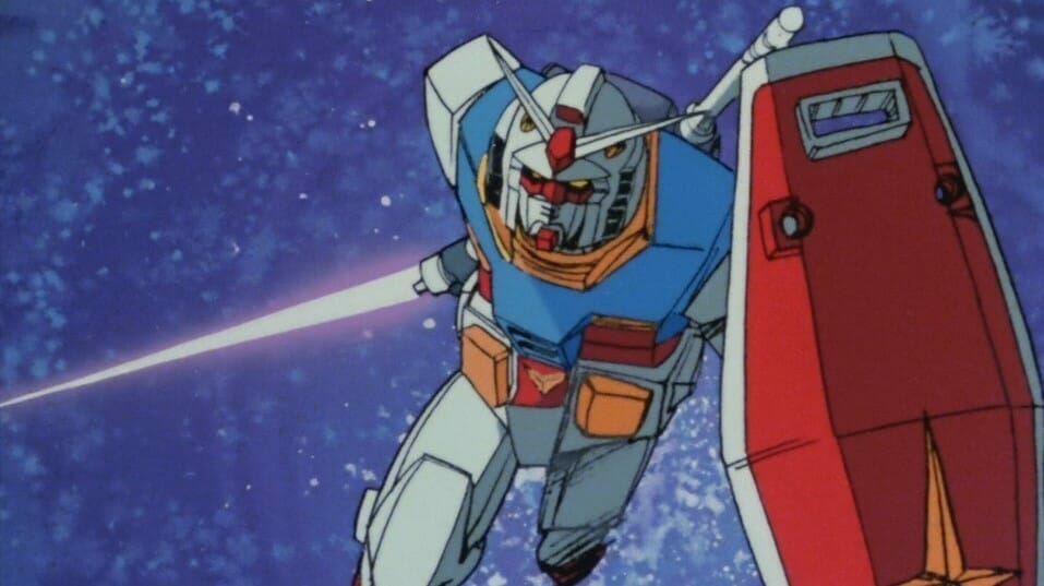 Front shot of the RX-78-2 Gundam, a white robot with red and blue accents, as it charges into battle. It is holding a shield and a laser sword.