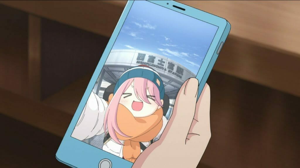 Still from Laid-Back Camp that depicts a hand holding a blue smartphone. The phone's screen has a selfie of Nadeshiko, who is smiling in front of Nishifujinomiya Station