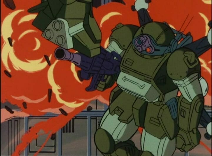 Still from Armored Trooper VOTOMS featuring a green robot holding a large gun as an explosion roils up behind them.