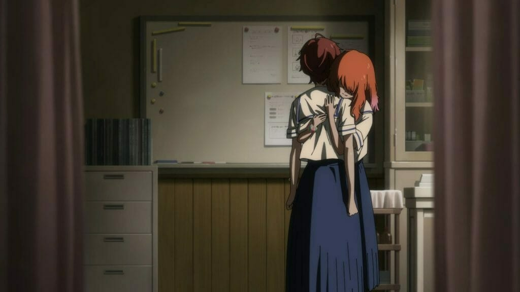 Two girls in a shadowy room. One is embracing the other, whose arms hang limp by her sides