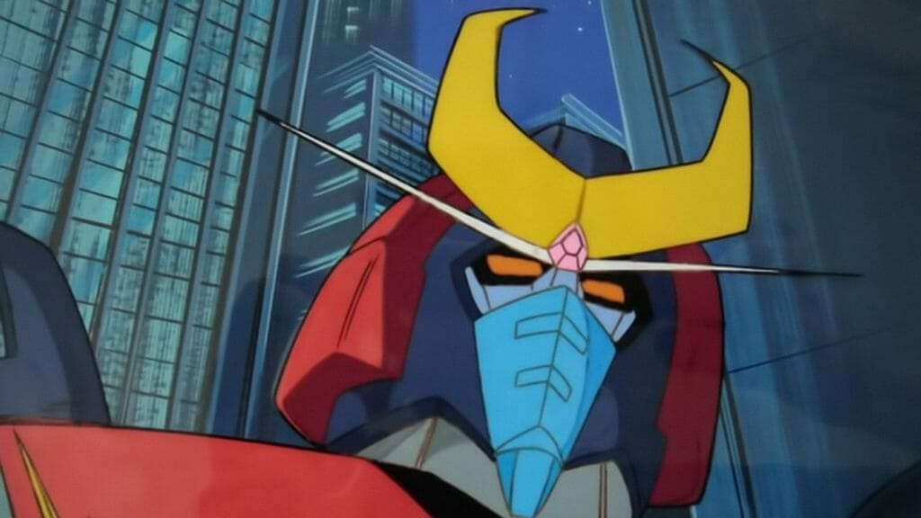Still from Space Warrior Baldios featuring a red, blue, and yellow robot standing before a city.