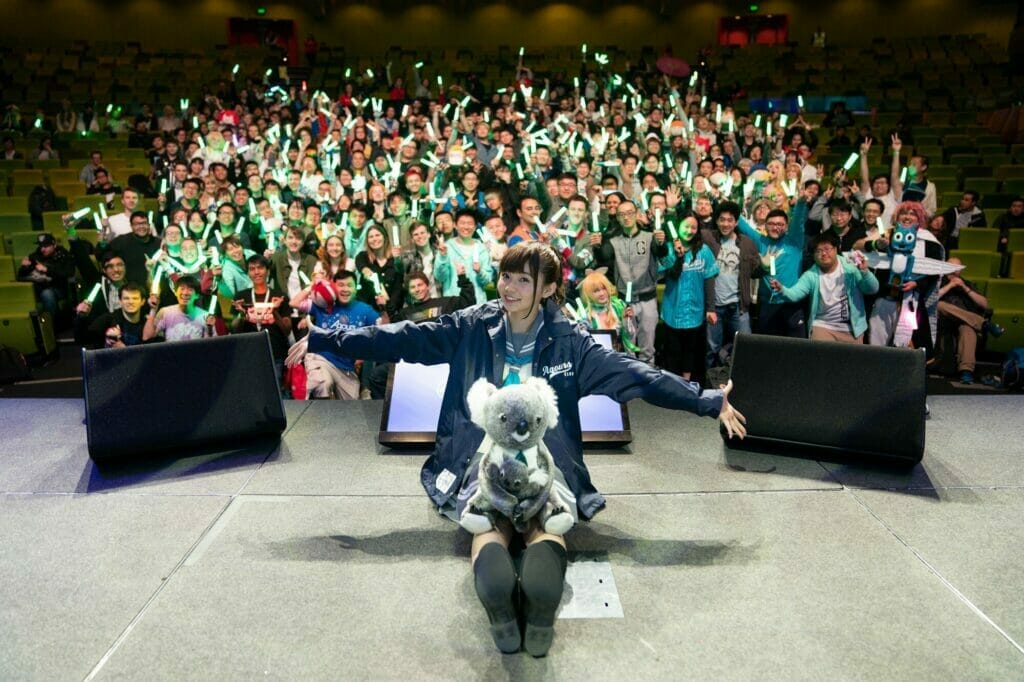 A Love Live voice actress sitting on stage with a koala plush in her lap. Behind her, an audience waves glowsticks