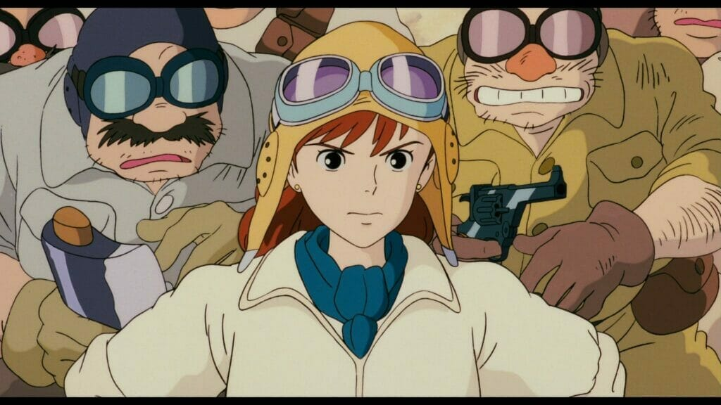 Still from Porco Rosso that focuses on a woman in a flight suit and aviator cap. She's standing, defiant, as several men look on nervously behind her.