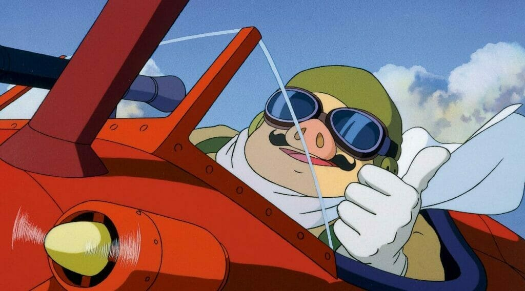 Still from Porco Rosso depicting a man with a pig-head seated in the cockpit of an airplane. He smiles as he gives a thumbs up.