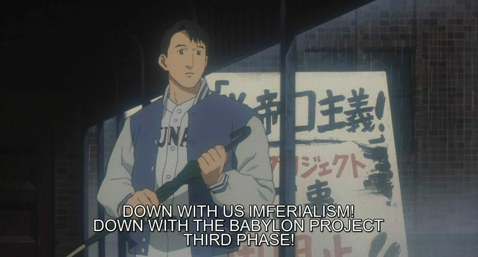 """Still from WXIII: Patlabor the Movie 3 that features a man standing in front of sign as he holds an umbrella. Sign text: """"DOWN WITH US IMFERIALISM! DOWN WITH THE BABYLON PROJECT! THIRD PHASE!"""""""