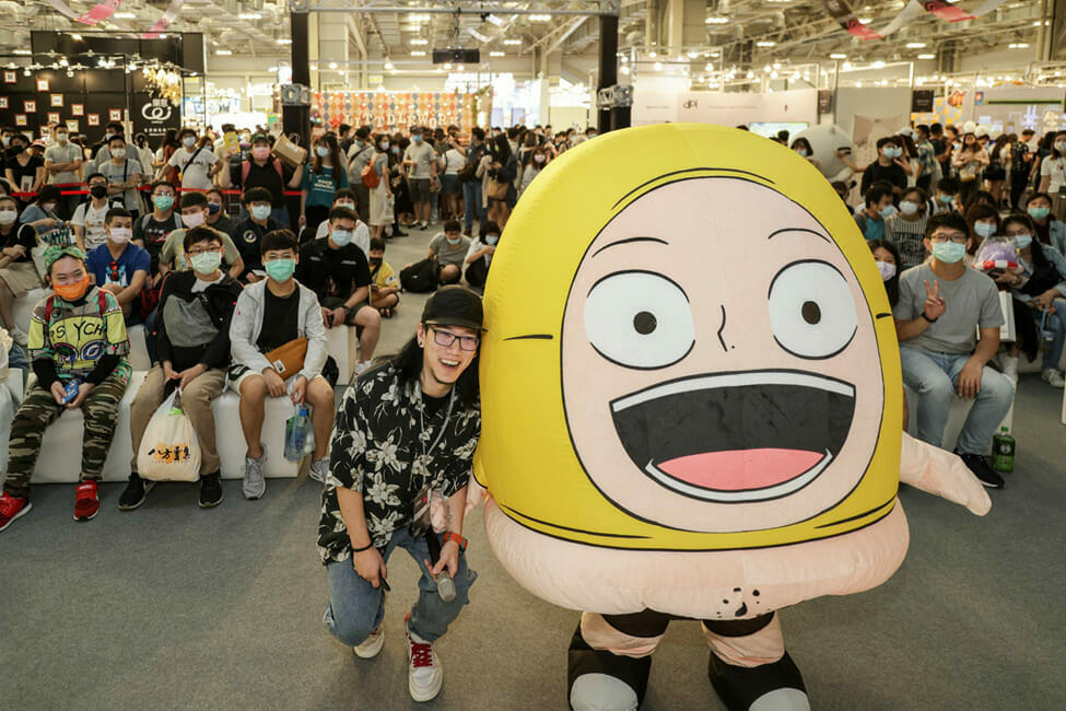 A man poses by a yellow mascot character, in front of an audience of onlookers.