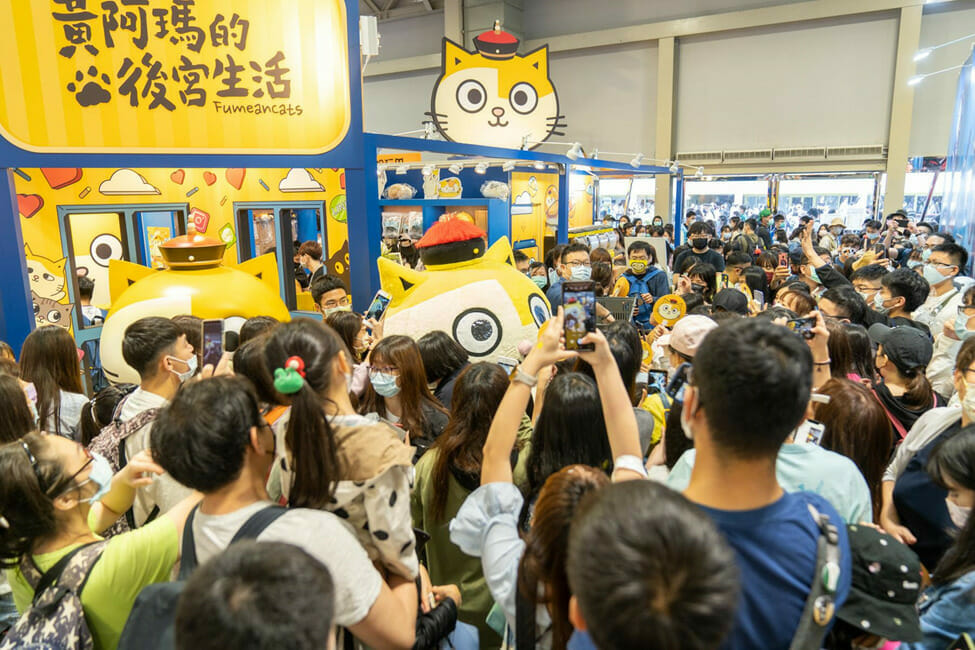 A mascot character of a yellow-and-white cat wearing a red hat stands amid a crowd of people