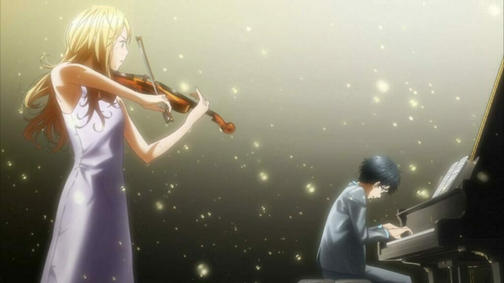 A man in a grey suit plays the piano, his back to a blonde woman clad in white, playing the violin. The two are lit from above by a spotlight.