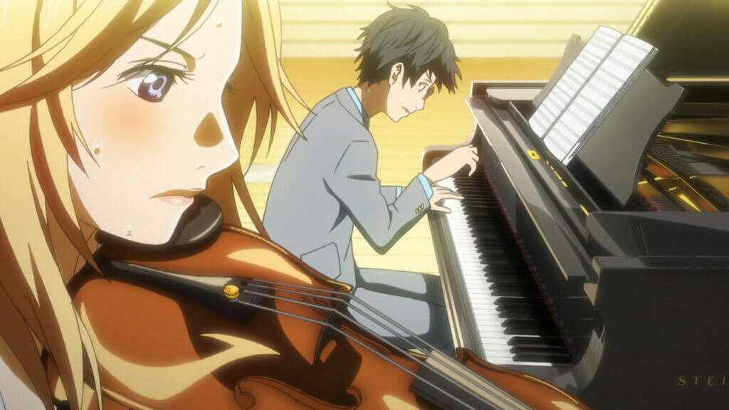 A man in a grey suit focuses on his music as he plays the piano. In the foreground, a blonde woman plays the violin, her face clearly showing intense focus.