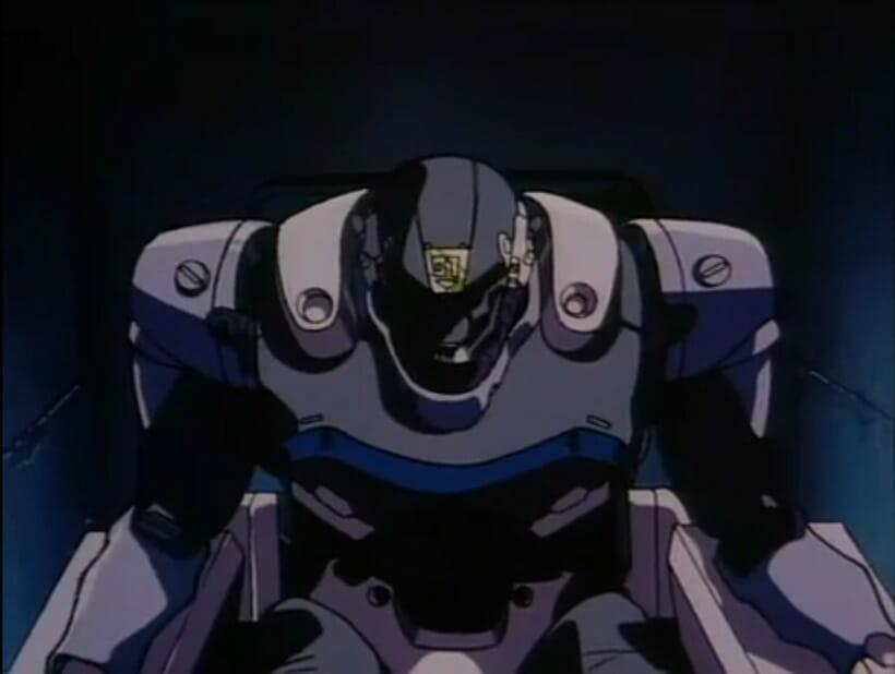 A hulking robot sits, staring menacingly forward.