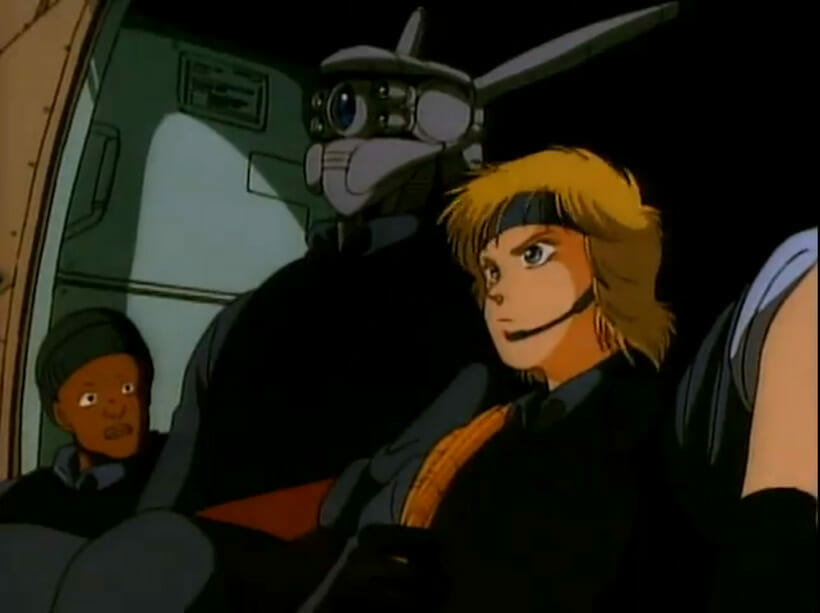 A blonde woman and a giant robot sit stoically as a man stares in shock.