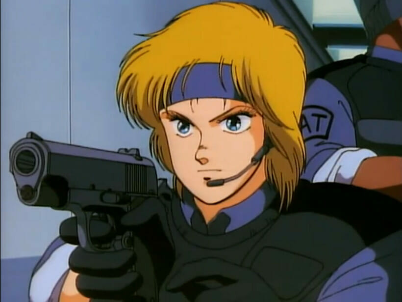 A blonde woman in armor points a gun at the camera.