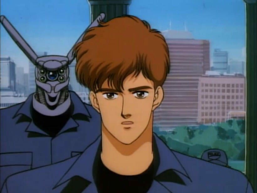 A brown-haired man stands before a giant robot in a jumpsuit. Both of them are facing the camera