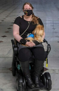Photograph of a blonde woman in a black shirt, sitting with a service dog.