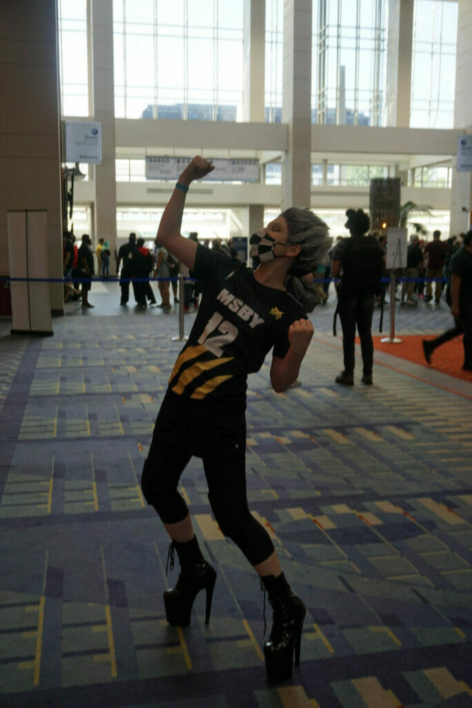 Photo from Otakon 2021 - A woman with short grey hear, wearing an MSBY jersey, poses triumphantly