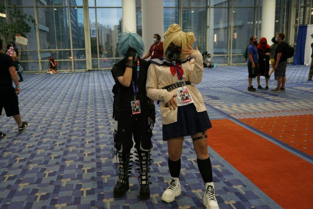Photo from Otakon 2021 - two individuals dressed as My Hero Academia characters pose for a photo.